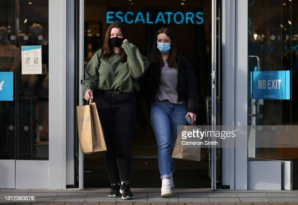 People leave Primark with bags as shops reopen after coronavirus restrictions ease on April 12, 2021 in Truro, England. England has taken a...