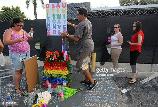People leave signs and flowers for the victims of the Pulse Nightclub shooting at the front of the nightclub building on June 21 2016 in Orlando...