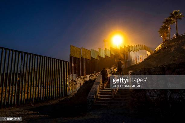 People leave the beach near the US/Mexico border fence in Playas de Tijuana Baja California state Mexico on August 10 2018 From the south border with...