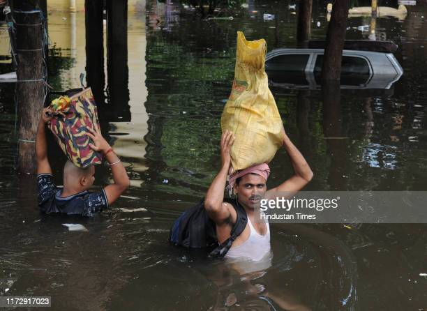 People leave their residences in the waterlogged area of Rajender Nagar on October 1 2019 in Patna India At least 28 people have so far lost their...