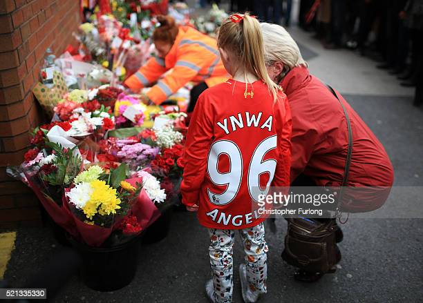 People leave tributes outside Anfield stadium before a memorial service to mark the 27th anniversary of the Hillsborough disaster on April 15 2016 in...
