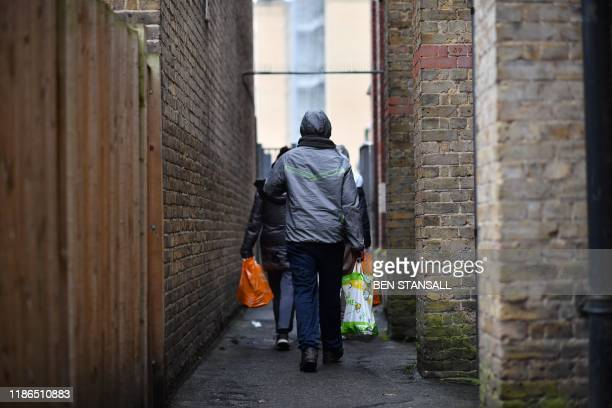 People leave with their food package after visiting the Slough Baptist Church food bank in Slough west of London on November 28 2019 As record...