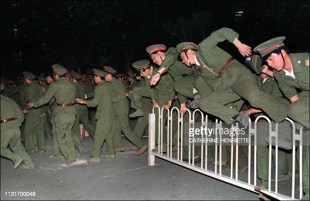 People Liberation Army soldiers leap over a barrier on Tiananmen Square in central Beijing 04 June 1989 during heavy clashes with people and...