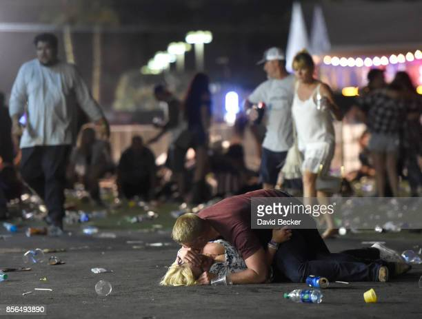 People lie on the ground at the Route 91 Harvest country music festival after apparent gun fire was hear on October 1 2017 in Las Vegas Nevada There...