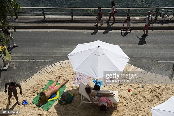 People lie on the sand of a temporary artificial beach set up on the banks of the river Seine as part of the 14th edition of Paris Plages on July 21...