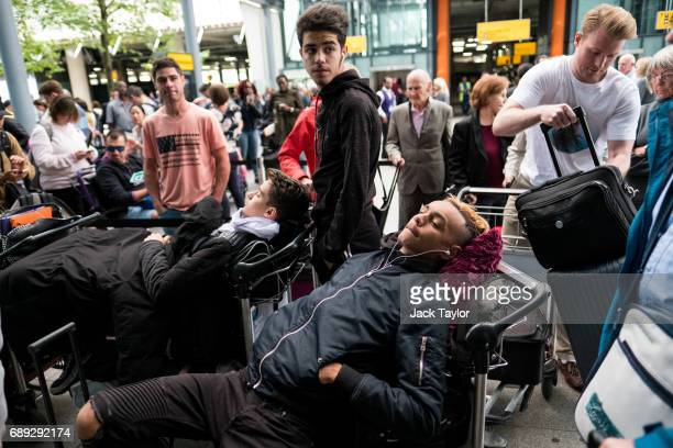 People lie on their luggage as they queue outside Heathrow Airport Terminal 5 on May 28 2017 in London England Thousands of passengers face a second...