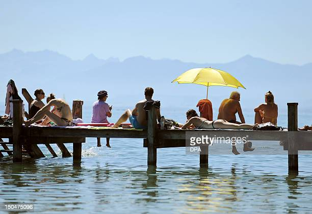People lie under a sun shade and sunbath on a bathing jetty on lake Starnberger See in Bavaria southern Germany on August 19 2012 Temperatures...