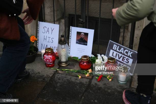 People light a candle in a small memorial for George Floyd in front of the United States of America Consulate on May 31 2020 in Krakow Poland The...