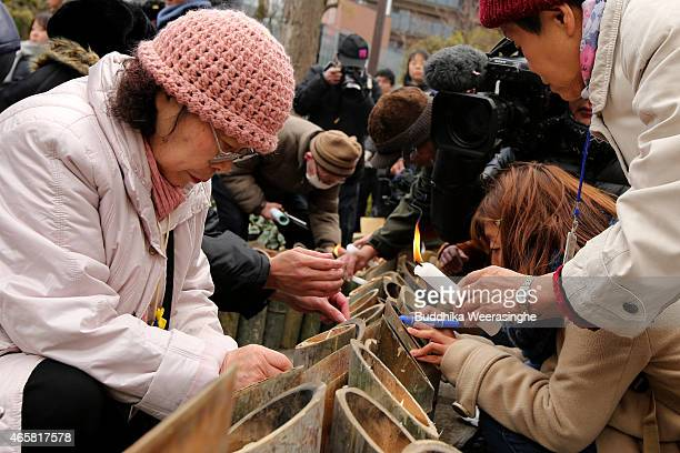 People light bamboo candles placed in the shape of the date 311 to commemorate the victims of Great East Japan Earthquake and Tsunami in front of...