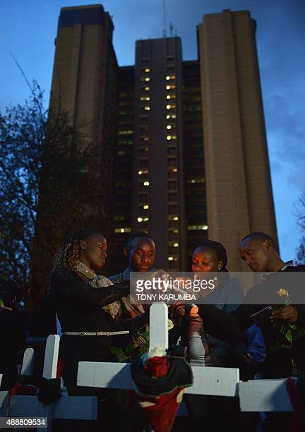 People light candles alongside wooden crosses at FreedomCorner in Uhuru Park in Nairobi on April 7 2015 during a candlelight vigil for the victims of...