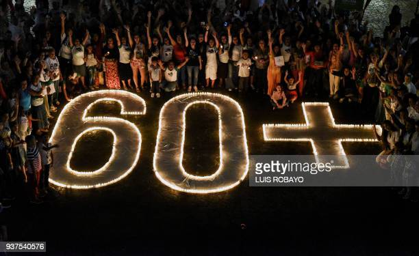 TOPSHOT People light candles and form the 60 sign during the Earth Hour environment campaign in Cali Valle del Cauca department Colombia on March 24...