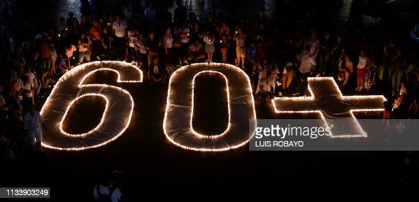 People light candles and form the 60+ sign on March 30, 2019 in Cali, Colombia, during the a Earth Hour organised by the green group WWF. - Earth...