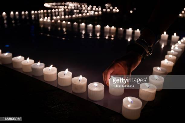 People light candles and form the 60 sign on March 30 2019 in Cali Colombia during the a Earth Hour organised by the green group WWF Earth Hour is a...