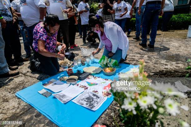 People light candles and lay flowers next to an antimonument placed by activists to mark the 10th anniversary of the San Fernando Massacre in which...