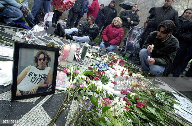 People light candles and leave flowers at Strawberry Fields in Central Park to mark the 20th anniversary of John Lennon's death