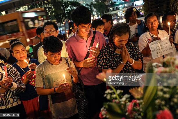 People light candles and pray for the victims of a bomb blast at the reopened Erawan shrine in Bangkok Thailand on Wednesday Aug 19 2015 Bangkok's...