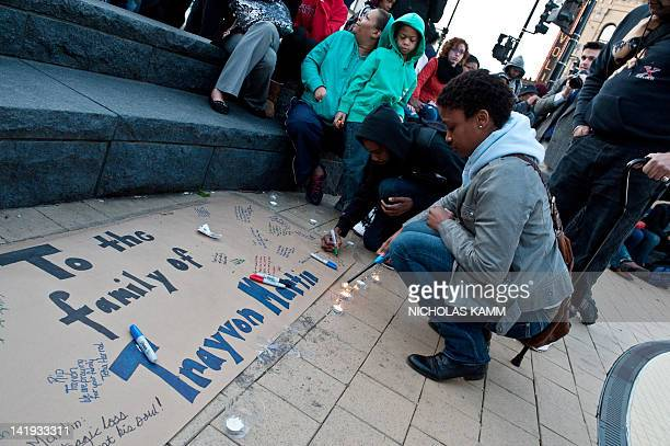 People light candles and write messages during a vigil in Washington on March 26, 2012 for Trayvon Martin, an unarmed black Florida teenager shot to...