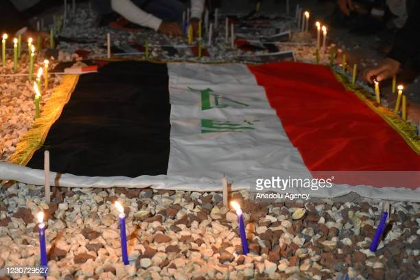 People light candles around the flag of Iraq to commemorate the twin suicide bombing attack at al-Tayaran Square in Baghdad carried out by Daesh...