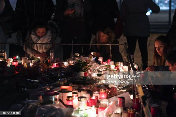 People light candles as they gather on December 13 in memory of the victims of the attack near the Christmas market of Strasbourg in eastern France...