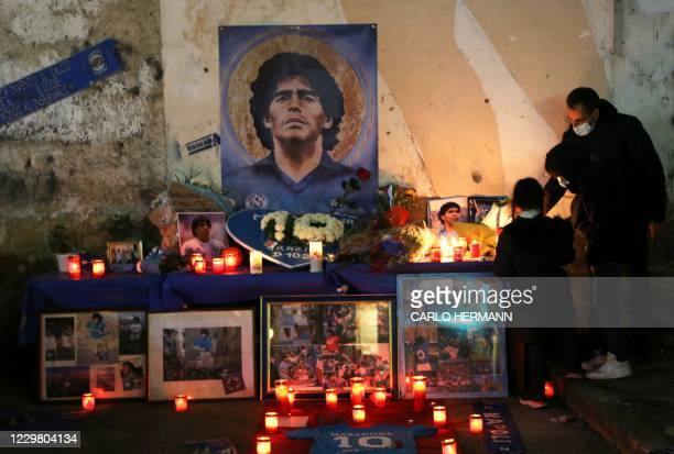 People light candles as they to mourn the death of Argentinian football legend Diego Maradona, on November 26, 2020 at a makeshift altar set up in...