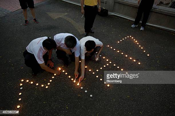 People light candles at a candlelight vigil for Malaysian Airline System Bhd flight MH17 in Kuala Lumpur Malaysia on Saturday July 19 2014 Flags in...