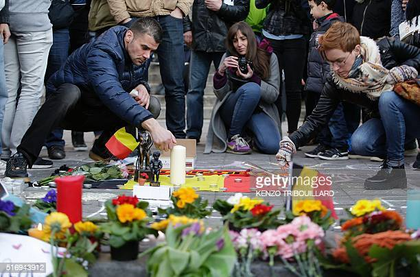 People light candles at a makeshift memorial at Place de la Bourse following attacks in Brussels on March 22 2016 Airlines cancelled hundreds of...