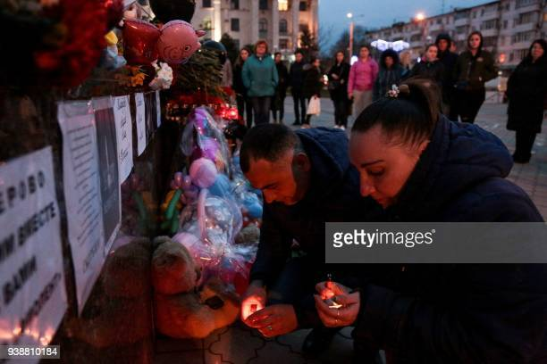 People light candles at a makeshift memorial in tribute to the victims of a Siberian shopping mall fire in Kemerovo in downtown Simferopol on March...