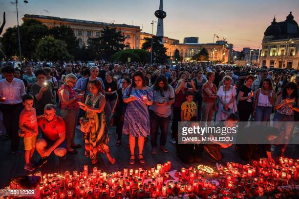 People light candles at a makeshift memorial site in front of the Romanian Ministry of Interior in Bucharest July 27, 2019 to commemorate Alexandra,...