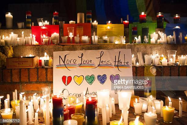 People light candles at a memorial gathering for those killed in Orlando at the Colonial Zone in Santo Domingo on June 14 2016 Fortynine people were...