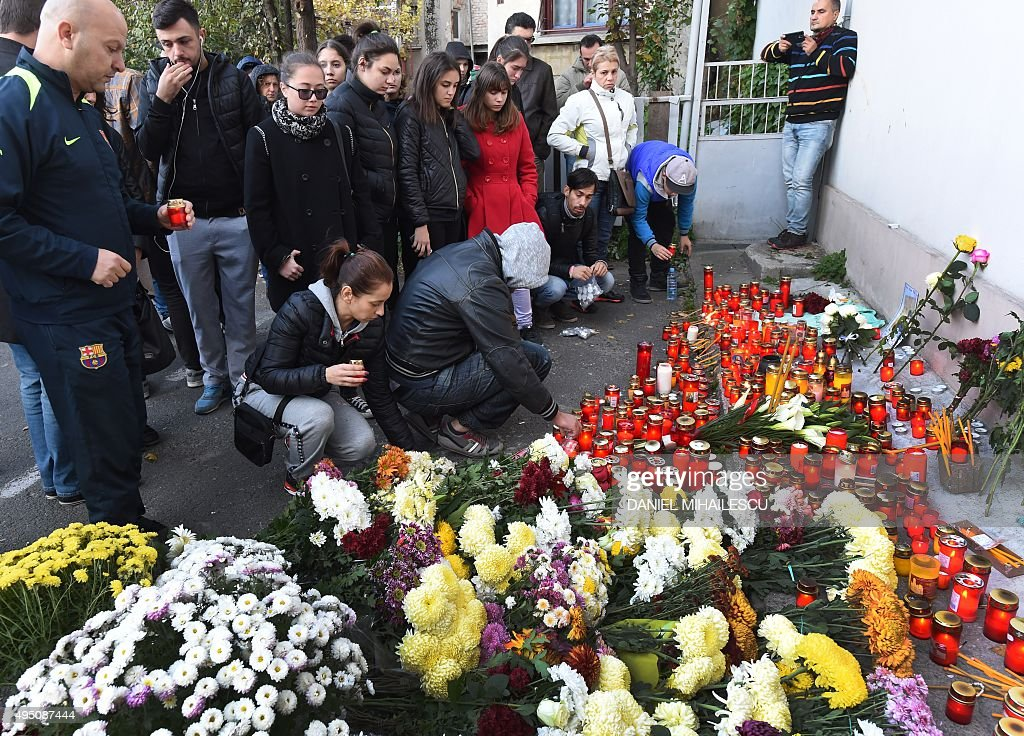 People light candles at a memorial makeshift outside the nightclub Colectiv in Bucharest on October 31, 2015, a day after a fire broke up. At least 27 people were killed and more than 160 injured after a fire ripped through a nightclub in Bucharest late on Friday, in one of the worst accidents to hit the Romanian capital. MIHAILESCU