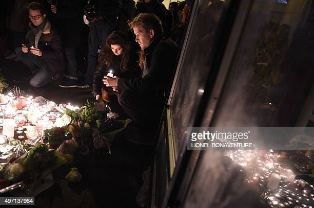 """People light candles at a pop-up memorial near the """"Belle Equipe"""" restaurant, the site of one of the attacks in Paris on November 14, 2015. Islamic..."""