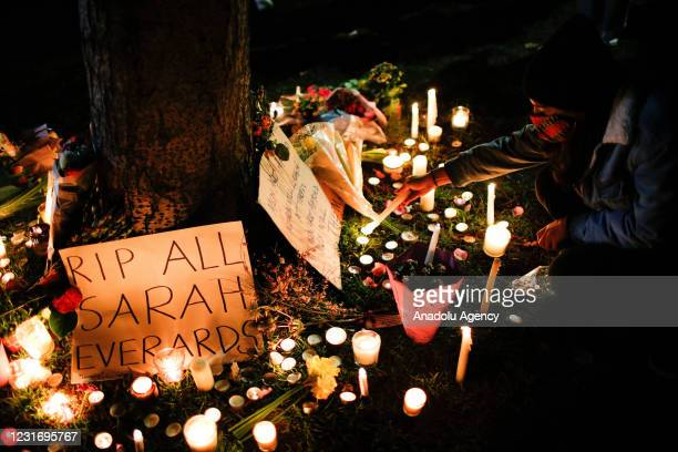 People light candles at the base of a tree as mourners for the life of murdered 33-year-old Sarah Everard, whose remains were found this week in...