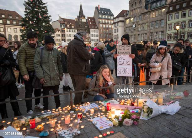 People light candles at the Christmas market where the day before a man shot 14 people killing at least three on December 12 2018 in Strasbourg...