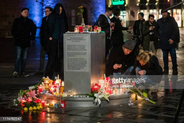 People light candles at the market place near to the scene of a shooting on October 9 2019 in Halle Germany Law enforcement authorities after...