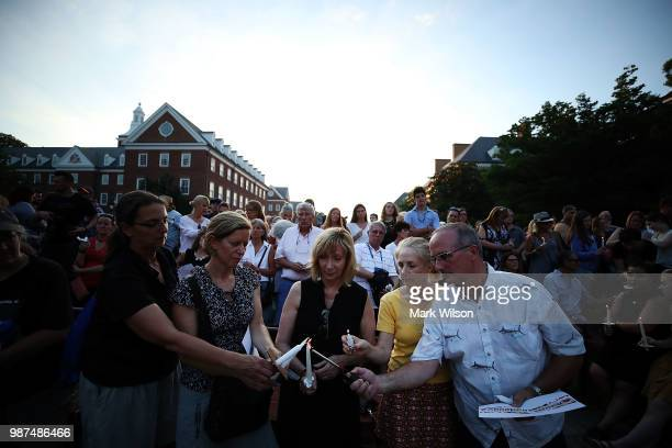 People light candles during a candlelight vigil to honor the 5 people were shot and killed at the Capital Gazette newpaper yesterday on June 29 2018...