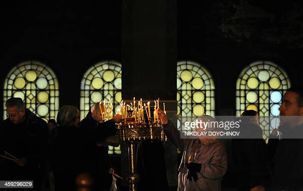 People light candles during a Christmas mass in the goldendomed Alexander Nevsky cathedral in central Sofia on December 25 2013 Bulgaria unlike some...