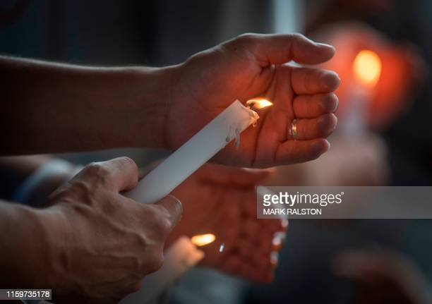 People light candles during a prayer and candle vigil organized by the city, after the shooting that left 20 people dead at the Cielo Vista Mall...