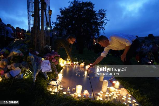 People light candles during a vigil in North Down Crescent Park in the Keyham area of Plymouth, southwest England, on August 13, 2021 in memory of...