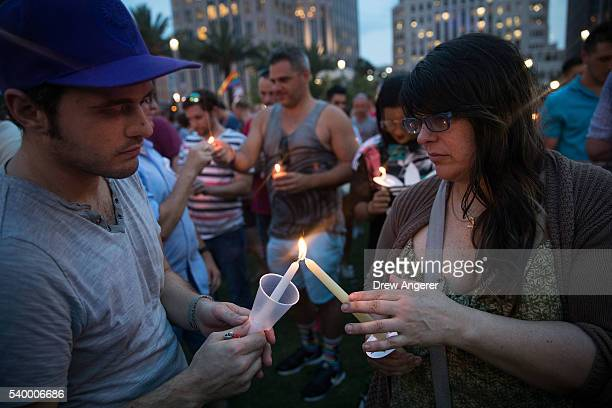 People light candles during an evening memorial service for the victims of the Pulse Nightclub shootings at the Dr Phillips Center for the Performing...