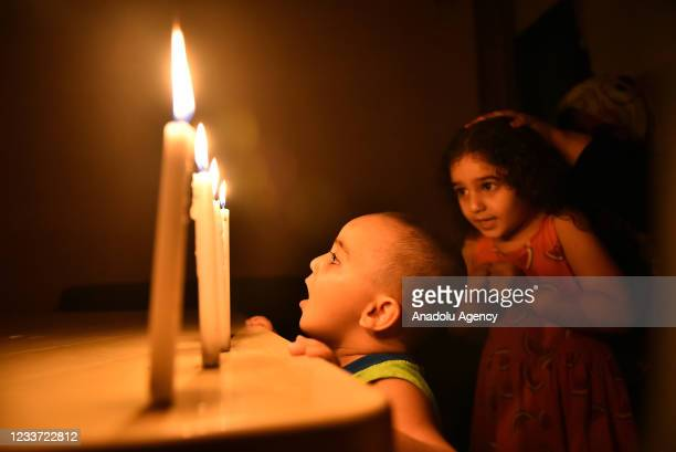 People light candles during power cuts due to the fuel shortage and problems in the supply of fuel, which is traded in dollars, in Beirut, Lebanon on...