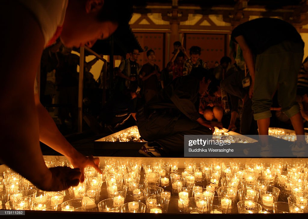 People light candles during the Tanabata festival at the Hatamono shrine on July 7, 2013 in Osaka, Japan. Tanabata is a Japanese star festival in which people wear traditional ''yukata'' robes and write their wishes on strips of paper to hang on bamboo trees.