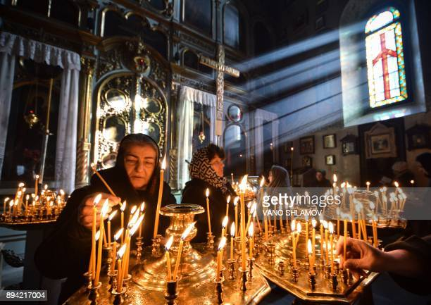 TOPSHOT People light candles in a church on December 17 2017 in downtown Tbilisi / AFP PHOTO / Vano Shlamov