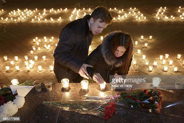 People light candles in Simferopol on November 1 2015 in memory of the victims of a jetliner crash Russia mourned its biggest ever air disaster after...