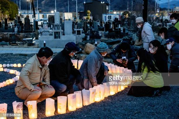 People light candles in the night as a symbol of light in the darkness in remembrance of those killed 10 years ago in front of the 'Ganbare...