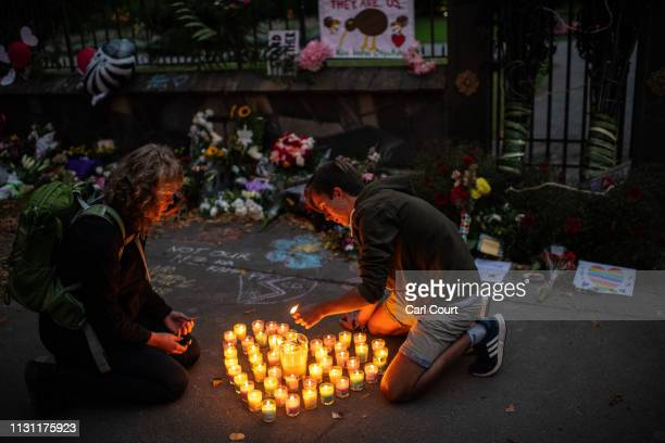 People light candles next to flowers and tributes laid by the wall of the Botanic Gardens on March 17 2019 in Christchurch New Zealand 50 people are...