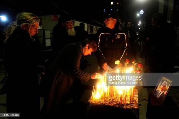 People light candles on the spot where leading Kosovo Serb politician Oliver Ivanovic was killed in a brazen driveby shooting in Mitrovica on January...