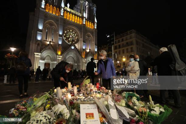 People light candles outside Notre-Dame de l'Assomption Basilica in Nice on October 31 to pay tribute to the victims two days after a knife attacker...
