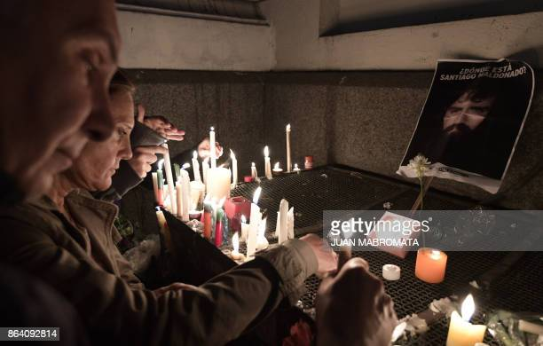 People light candles outside the judicial morgue where an autopsy of the corpse of Santiago Maldonado disappeared on August 1st during a Mapuche...
