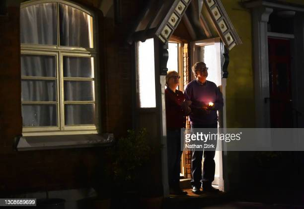 People light candles outside their homes to pay their respects on the National Day of Reflection on March 23, 2021 in Lichfield, England. Marie Curie...