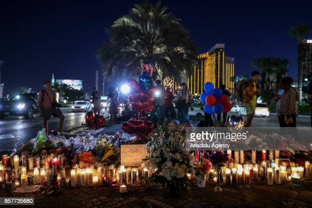 People light candles place figures and flowers at a makeshift memorial set up along the Las Vegas Strip for the Las Vegas mass shooting victims who...
